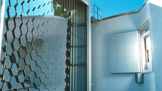 DLR-Sonnenofen in Köln: Ein 60 Quadratmeter großer Spiegel sammelt das Sonnenlicht und lenkt es auf die Facettenspiegel (links). Diese Spiegel konzentrieren die Sonnenstrahlen um den Faktor 5200 und lenken sie in das Versuchslabor des Kölner Sonnenofens des Deutschen Zentrums für Luft- und Raumfahrt.