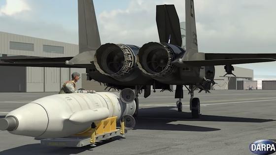 Arbeiter befestigen das Satellitenträgersystem unter dem Kampfjet. Derzeit dürfen die geladenen Minisatelliten maximal 50 Kilogramm schwer sein.