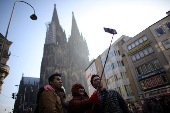 Ausländische Touristen fotografieren sich mit einem Smartphone vor dem Kölner Dom. Seit Smartphones mit Apps ausgestattet sind, über die man das gestohlene Handy aufspüren oder aber blockieren kann, sind die Diebstähle stark rückläufig.