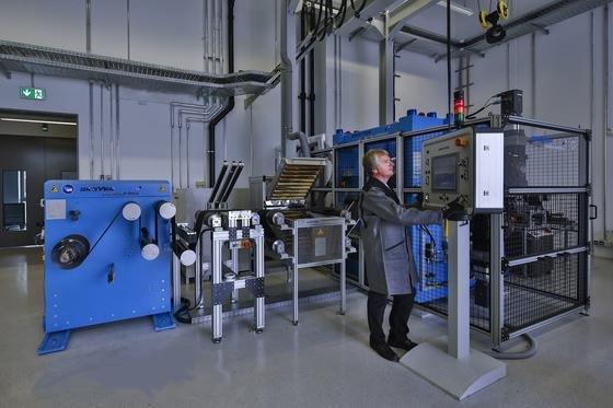 Ein Mitarbeiter der Forschungseinrichtung ZSW steht vor einem so genannten Präzisions-Kalander, der zur Verdichtung der Elektroden dient.
