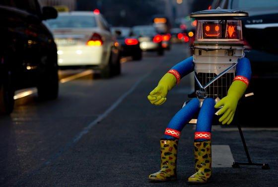 """""""Nehmt mich mit"""": Roboter hitchBOT sitzt am 12. Februar 2015 in München am Straßenrand – und lächelt in die Kamera. Denn so allein, wie´s aussieht, ist er nicht. Seit seiner Reise durch Kanada ist er ein Medienliebling. Was seine Fans aber zunehmend stört."""