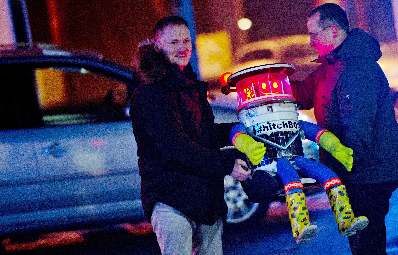 Martin (li.) und Bernd laden hitchBOT am 13. Februar in München in ihr Auto ein. Von dort aus startete der trampende Roboter eine zehntägige Tour durch Deutschland. Im Sommer 2014 hatte die Maschine per Anhalter bereits gut 6000 Kilometer durch Kanada zurückgelegt.