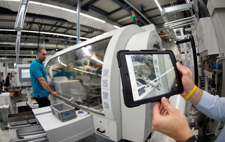 Immer mehr Unternehmen bereiten sich auf Industrie 4.0 vor: Ein Mitarbeiter des Antriebsspezialisten Wittenstein scannt im Zahnradwerk in Fellbach (Baden-Württemberg) mit einem Tablet PC einen Barcode an einer Maschine. Informationen über Arbeitsanweisungen werden in der Produktion nicht mehr per Handzettel, sondern digital weitergegeben.