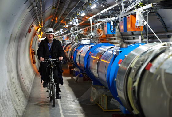 Ingenieur Andrzej Siemko radelt neben dem LHC (Large Hadron Collider). Das Bild wurde Ende November 2013 aufgenommen.