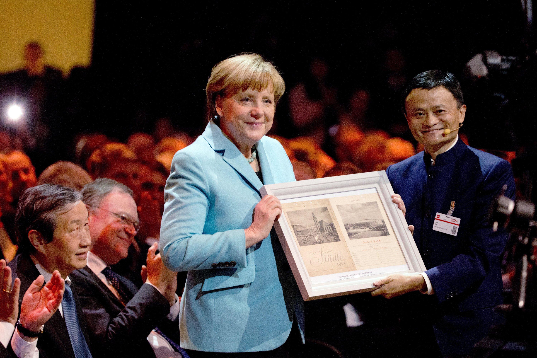 Jack Ma (re.), Gründer und CEO des Internetkonzerns Alibaba Group, überreicht Bundeskanzlerin Angela Merkel am 15. März 2015 während der Eröffnung der weltweit größten Computermesse CeBIT ein Geschenk neben Chinas Vize-Ministerpräsident Ma Kai (li.) und Stephan Weil (SPD), Ministerpräsident von Niedersachsen. F