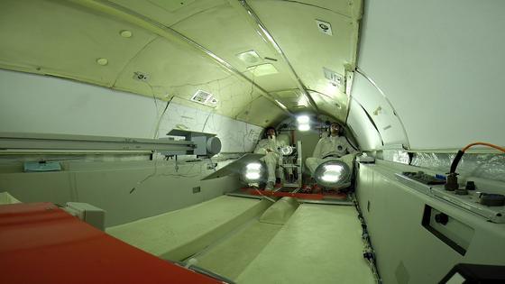 Zwei Forscher schießen in der Schwerelosigkeit bei einem Parabelflug Versuchsnetze auf ein Zielobjekt ab.