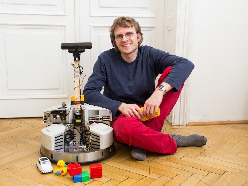 Squirrel-Projektleiter Michael Zillich mit seinem Roboter, der ordentlich aufräumen lernen soll.