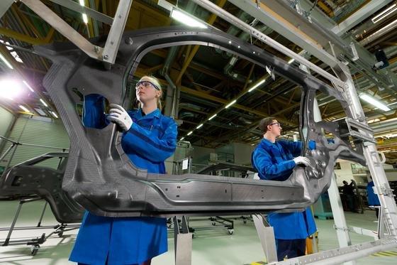 Eine Frau und ein Mann bereiten im BMW-Werk Landshut ein CFK-Karosserieteil für die Endbearbeitung durch Wasserstrahlschneiden vor: BMW setzt sich zum Ziel, dass der Frauenanteil im gesamten Konzern auf 17 % steigt.