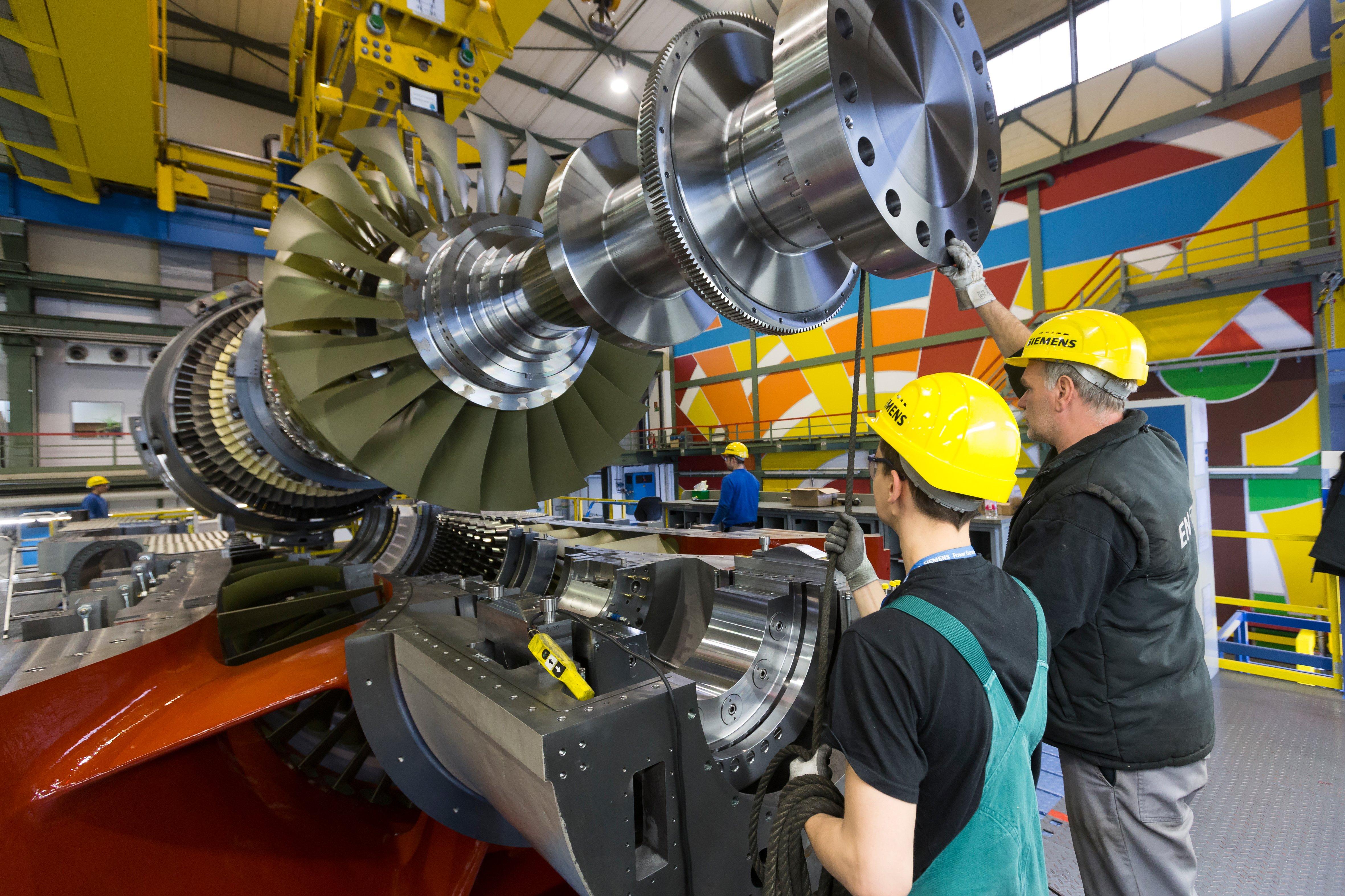 Millimeterarbeit bei der Montage der SGT5-8000H: Mitarbeiter des Gasturbinenwerks Berlin legen den so genannten Läufer in das Turbinengehäuse ein.