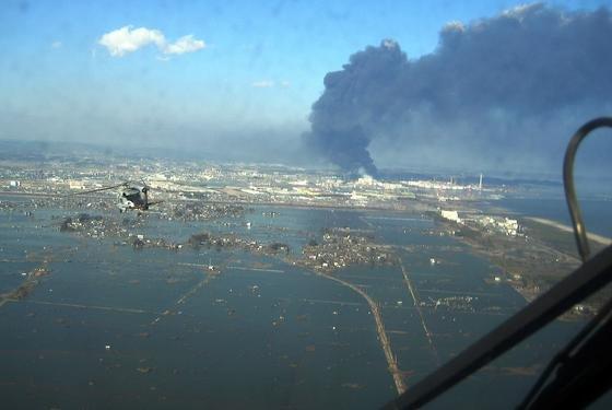 Sendai, rund 1000 Kilometer nördlich von Tokio, fotografiert aus einem Helikopter der US Navy am 12. März 2011: Durch den Tsunami am 11. März 2011 wurde die Hafenstadt stark zerstört, obwohl sie von einer sechs Meter hohen Mauer geschützt wurde. Im Hintergrund brennt eine Industrieanlage. Japanische Forscher haben jetzt herausgefunden, dass durch die Zerstörungen auch erhebliche Mengen klimaschädlicher Gase freigegesetzt wurden.