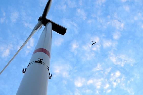 Ein Flugzeug über dem Windpark Langenhorn, der als erster Windpark Deutschlands mit dem System Airspex ausgestattet wurde. Eine Radarantenne ist am Turm der Windenergieanlage zu sehen.