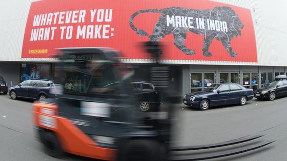 """Gut gebrüllt Löwe: Ein Gabelstapler fährt an einem Banner """"Make in India"""" beim Aufbau für die Hannover Messe in Hannover vorbei."""
