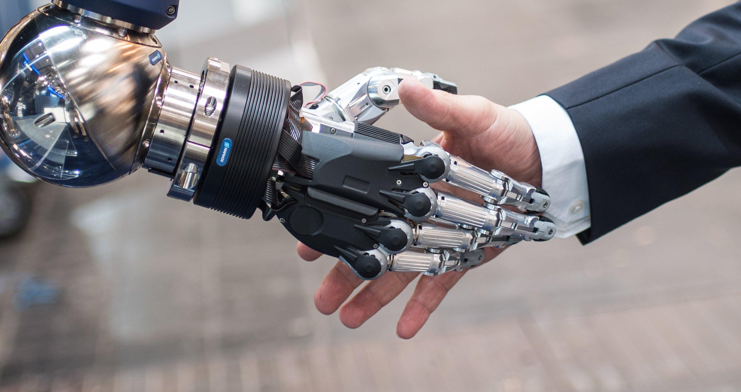 Ein Mann schüttelt auf der Hannover Messe am Stand des Greifsystem-Herstellers Schunk eine künstliche Hand.
