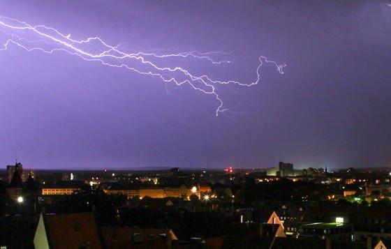 Ein Blitz erleuchtet in der Nacht über Nürnberg den Himmel.