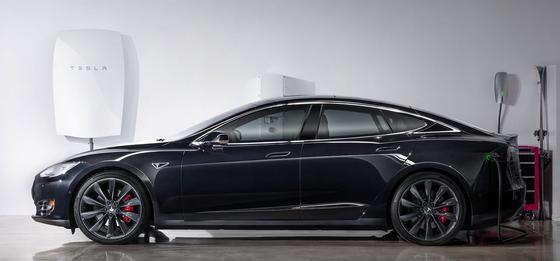 Die Vision von Elon Musk: An der Wand hängt die neuartige Hausbatterie Powerwall, die Solar- und Windstrom speichert. Passenderweise ließe sich damit direkt das Tesla Elektroauto tanken.