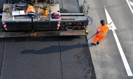 Straßenarbeiter bringen eine Asphaltdecke auf: Das Bitumen –also die klebrige Masse, in die der Splitt eingebettet ist –gewinnt man bislang aus Erdöl. Mikroalgen könnten eine ressourcenschonende Alternative sein.