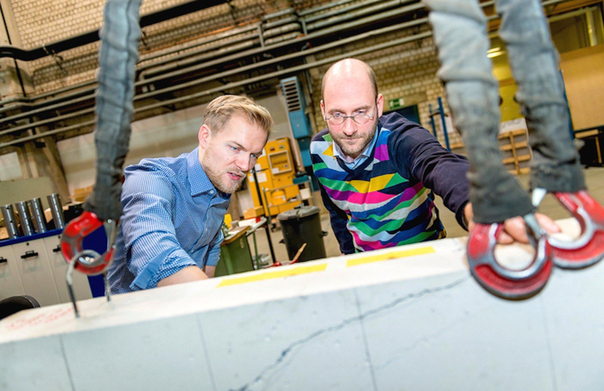 David Sanio (links) und Mark Alexander Ahrens begutachten einen Testbalken aus Beton im Labor. Hier wurde die Messtechnik geprüft.