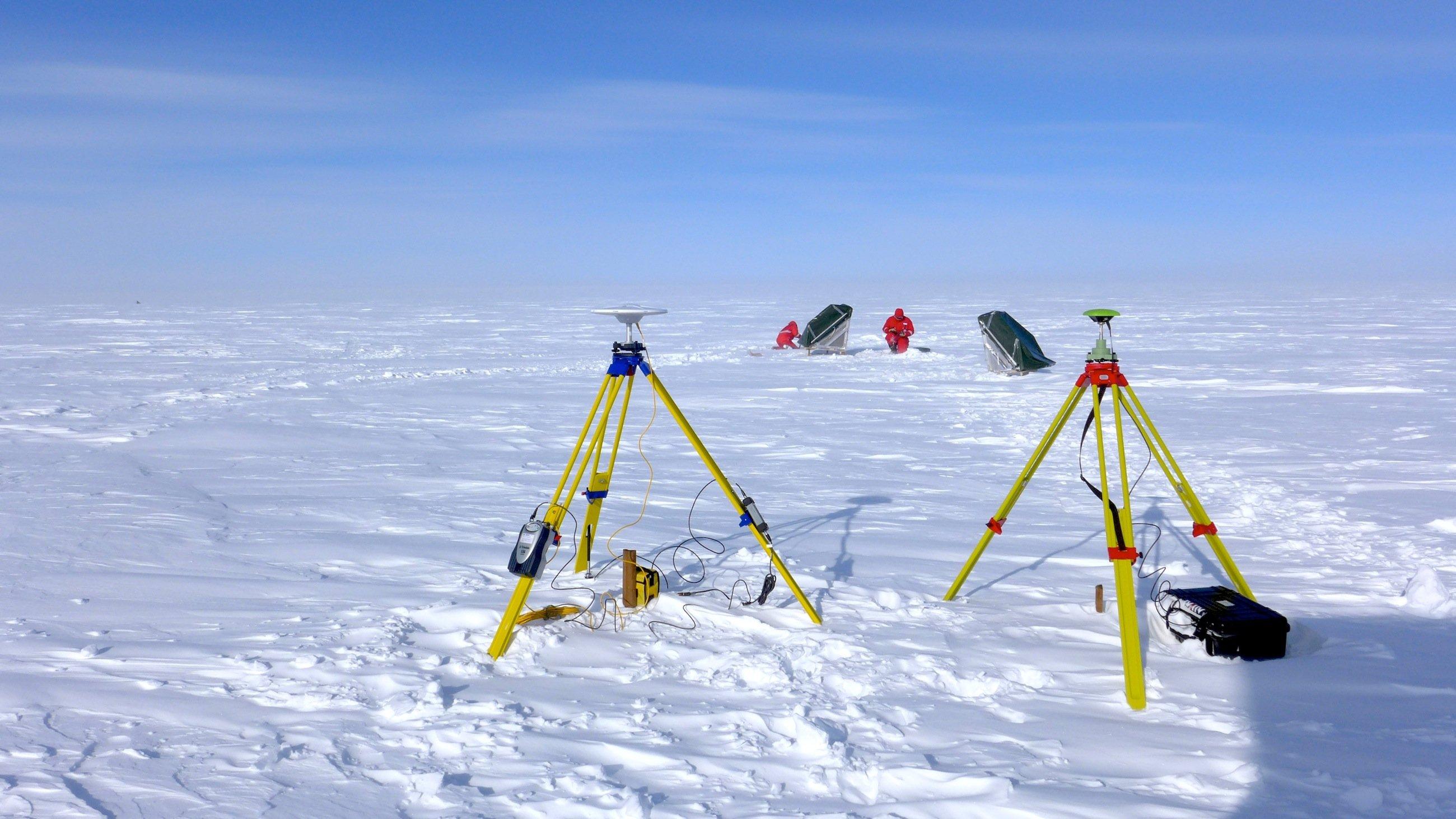 Die DLR-Wissenschaftler Martin Keller und Georg Fischer verankern zwei Radar-Reflektoren auf dem grönländischen Eisschild. Im Vordergrund sieht man zwei GPS-Basisstationen, die die präzise Vermessung der Reflektoren ermöglichen.