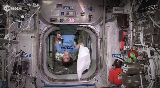 """Astronautin Samantha Cristoforetti winkt mit ihrem Handtuch in die Kamera. Zuvor hatte sie rund fünf Minuten aus dem Buch """"The Hitchhiker's Guide to the Galaxy"""" vorgelesen – ihr persönliches Gedenken an Kultautor Douglas Adams."""