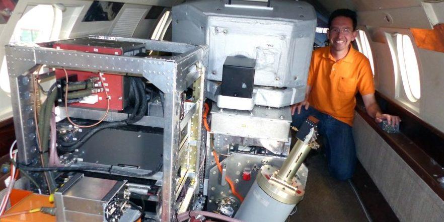 DLR-Projektleiter Dr. Oliver Reitebuch neben dem neuen Wind-Lidar-Gerät in der Falcon, mit dem die Winde bei Island und Grönland vermessen werden.