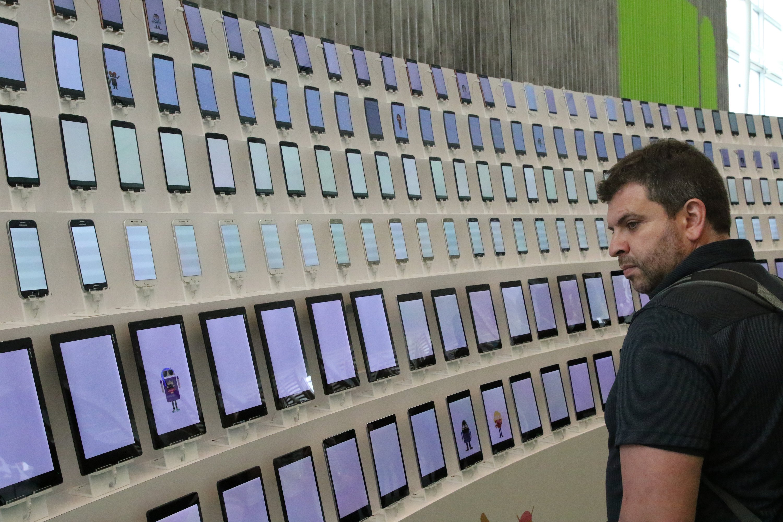 Ein Teilnehmer der Entwicklerkonferenz Google I/O 2015 betrachtet eine Sammlung von Android-Geräten. Das Spektrum reicht von Smartphones über so genannten Phablets bis hin zu größeren Tablet-Computern.