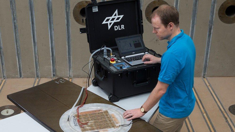 DLR-Forscher Markus Kaden demonstriert, wie mit Hilfe der mobilen Reparaturstation Strukturen aus faserverstärkten Kunststoffen schnell und effizient geflickt werden können.