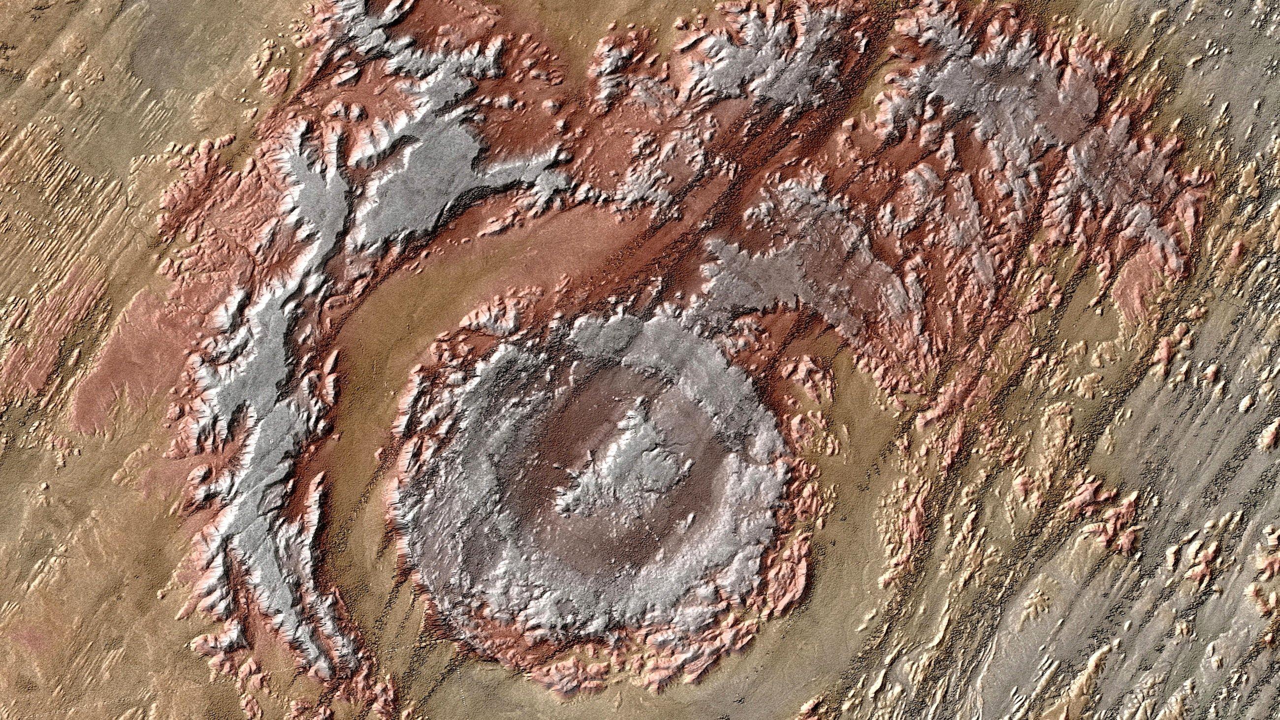 Diese Aufnahme zeigt die Aorounga-Struktur im nordafrikanischen Tschad. Sie dürfte bereits 345 Millionen Jahre alt sein und ist dementsprechend sehr stark verwittert. Gerade aus dem All sind sowohl der äußere als auch der innere Ring zu erkennen. Der kräftige Wind hat dabei wie ein Baumeister parallele Strukturen hinzugefügt. Sie bestehen aus windbeständigen Felsrücken, den sogenanten Yardangs, zwischen denen Sanddünen vom Wind getrieben hindurchwandern.