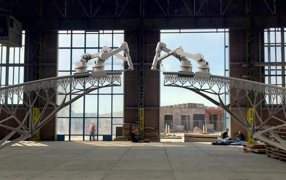 Simulation eines Brückenbaus per Roboter: Die Roboter fahren auf den von ihnen selbst gefertigten Stahlelementen. Der 1500 °C heiße Stahl wird praktisch in die Luft gespritzt und erstarrt.
