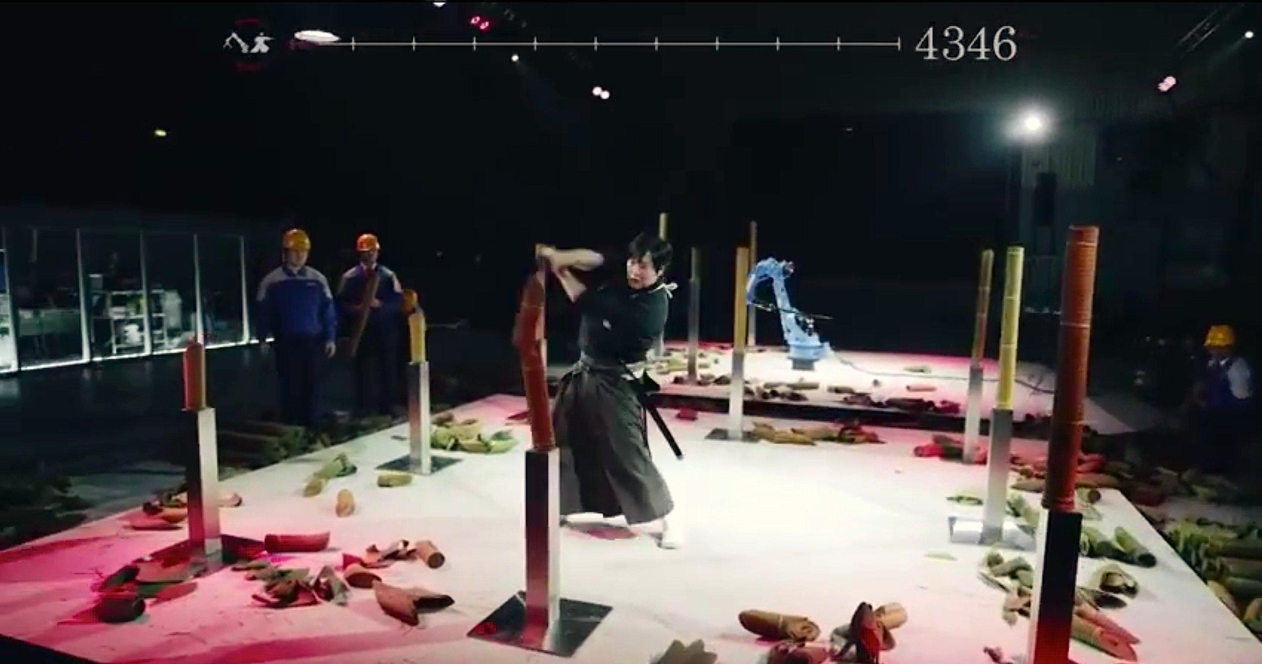 Nach dem Finale: Samurai Isao Machii und der SchweißroboterMotoman-MH24 haben zusammengerollte Bastmatten in Tausende von Stücken zerschnitten.
