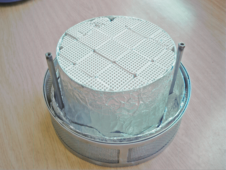 Ein Zeolithwabenkörper aus binderfreiem Material, eingepasst in einen Laborspeicherkorb.
