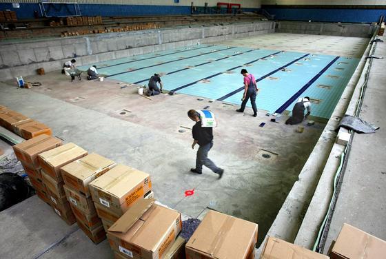 Sanierung eines Hallenbades: Beim Abschlagen alter Fliesen können Asbestfasern freiwerden. Fliesenkleber enthielt bis 1993 teilweise Asbestfasern.