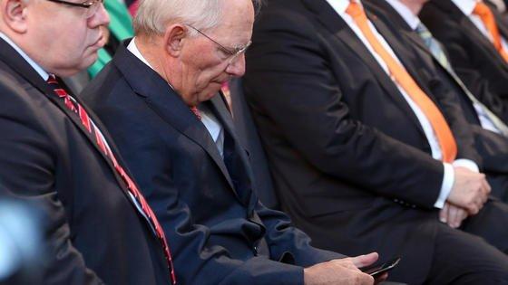 Auch Bundesfinanzminister Wolfgang Schäuble (2.v.l.) muss aufpassen: Bei exzessiver Nutzung des Smartphones mit unnatürlicher Kopfhaltung droht der Handynacken.