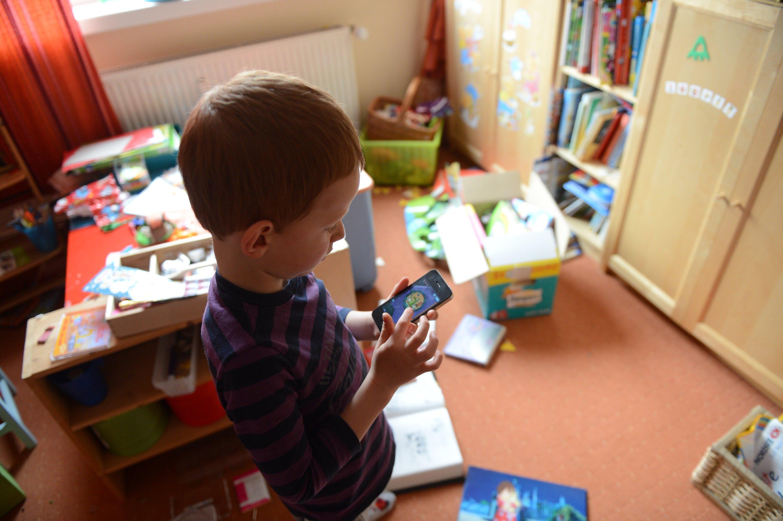 Ein Kind spielt mit dem Smartphone: Automatisch nimmt es eine unnatürliche Kopfhaltung ein. Sie belastet die Wirbelsäule stark und führt schlimmstenfalls zum Buckel.