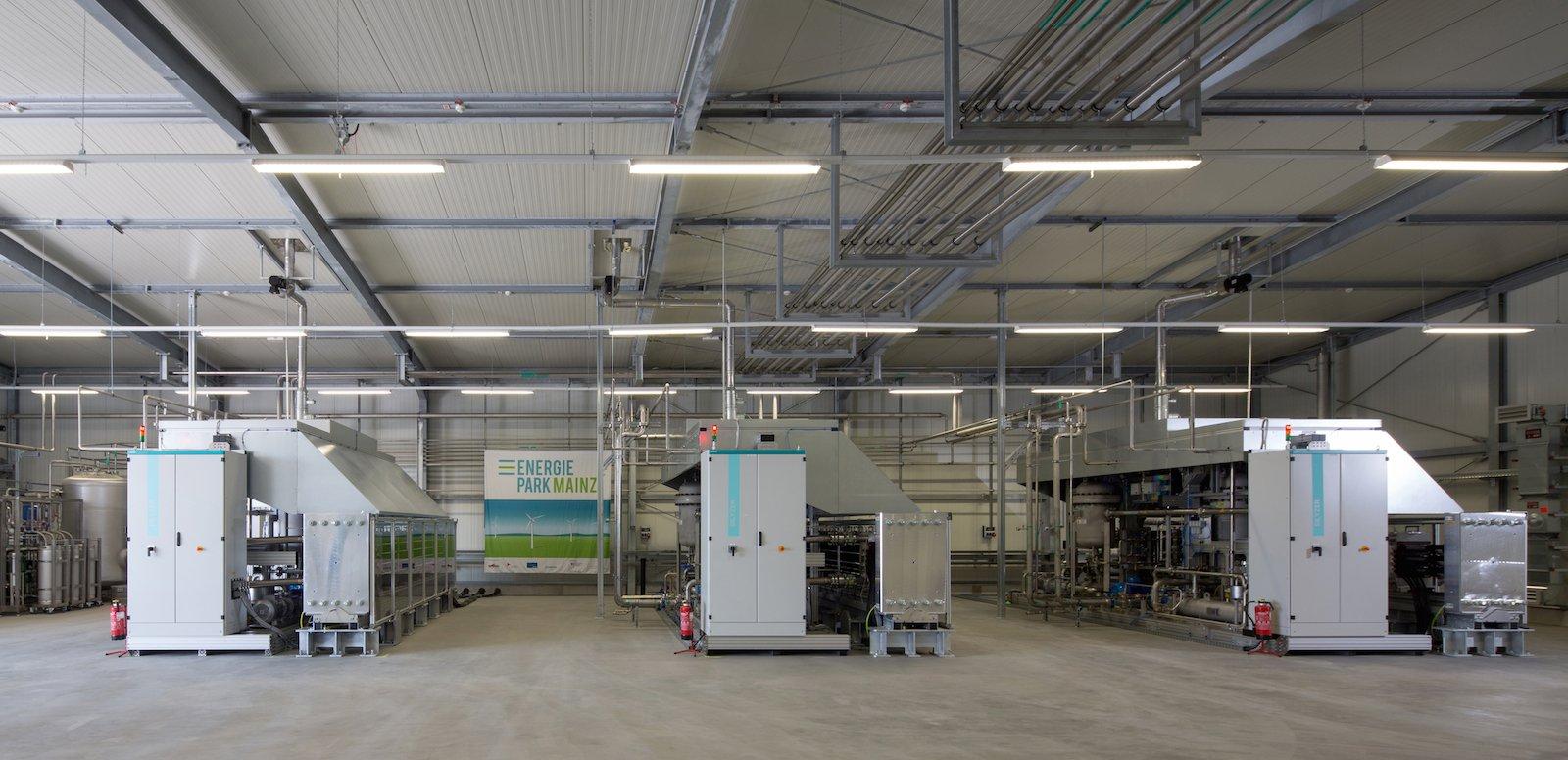 In der Elektrolysehalle erzeugt ein Wasserstoff-Elektrolysesystem von Siemens Wasserstoff aus Stromüberschüssen. Die PEM-Druckelektrolyse mit bis zu 6 MW Stromaufnahme ist weltweit die größte dieser Art. Der Energiepark hat damit die richtige Größe, um das Stromangebot kleinerer Windparks zu verstetigen.