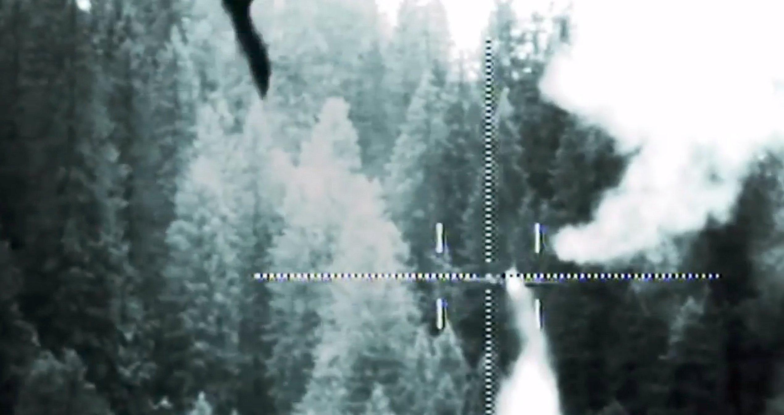 Abschuss eines Flugzeuges mit einem Hochenergielaser von Rheinmetall in den Schweizer Bergen. Das getroffene Flugzeuge ist rechts im Bild zu sehen. Zwei Rauchwolken sind deutlich zu sehen.