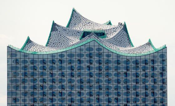 Winzig wirken die Bauarbeiter, die am 15.07.2015 auf dem Dach der Elbphilharmonie zu sehen sind. Erstmals seit Baubeginn ist das Konzerthaus frei von Baukränen. Das Gebäude soll im Januar 2017 eröffnet werden.
