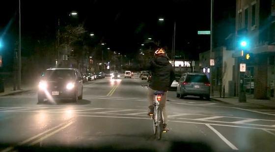 Abbiegen mit dem Lumos-Fahrradhelm: Die ausgestreckte linke Hand des Radfahrers ist kaum zu sehen, sehr wohl aber das Blinklicht, das nach links zeigt.
