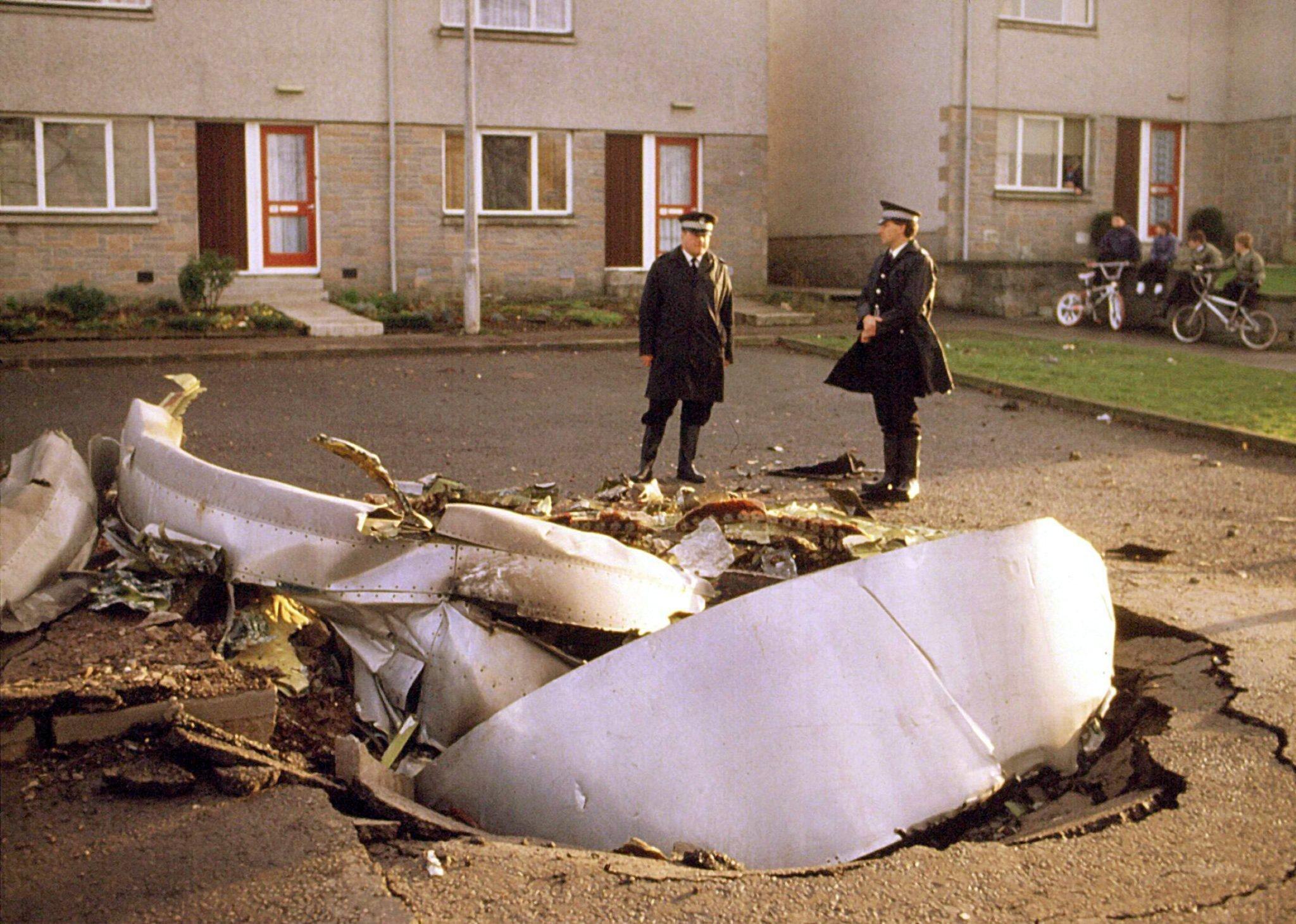 Zwei Polizisten stehen am 21. Dezember 1988 im schottischen Lockerbie hinter den Trümmerteilen eines Triebwerks der Passagiermaschine der amerikanischen Fluggesellschaft PanAm, die durch eine Bombenexplosion abgestürzt war.
