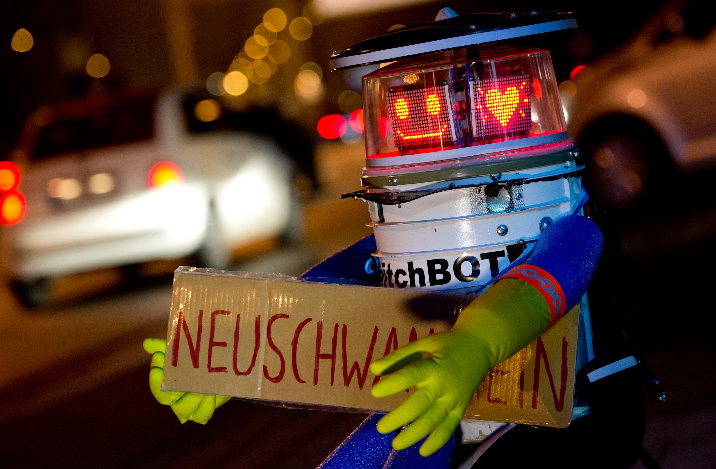 Da war die Roboterwelt noch in Ordnung: hitchBOT sitzt am 13. Februar 2015 in München mit einem Schild mit der Aufschrift