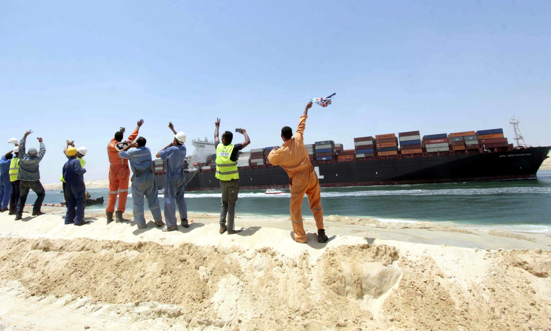 Vorgefeiert: Ägyptische Baurbeiter winken am 25. Juli 2015 freudig einem Container-Schiff, das testweise über den neuen zweispurigen Suezkanal fährt.