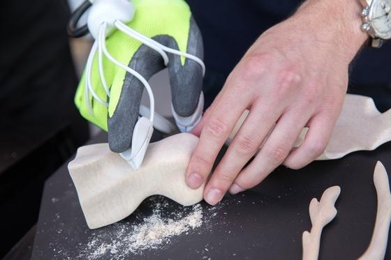 Mit dem HandschuhHapparatus kann man harte Materialien wie Stein und Holz bearbeiten. An den Fingerkuppen sind kleine Polster mit Schleifpapier montiert, die von einem kleinen Elektromotor bewegt werden.
