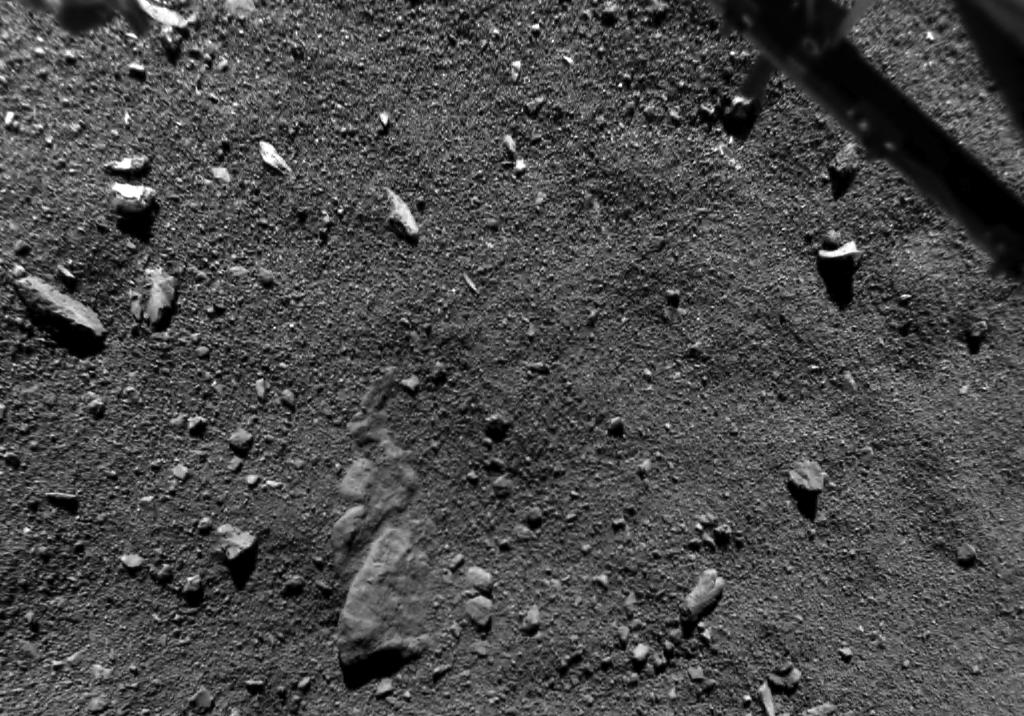 Dieses Bild der Tschuri-Oberfläche hat die Rolis-Kamera des Landers Philae am 12. November 2014 aus 67,4 m Höhe aufgenommen, während des Landeanfluges auf den Kometen. Ein Teil des Landegestells ist im Bild rechts oben erkennbar. Gut zu sehen ist die Kometenoberfläche mit unerwartet grobem Material und einem 5 m hohen Brocken. Die Rolis-Kamera wird unter der wissenschaftlichen Leitung der Deutschen Zentrums für Luft- und Raumfahrt (DLR) betrieben.