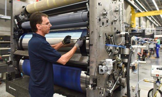 Ein Mitarbeiter verschraubt im Stammwerk des Maschinenbauers Heidelberger Druck Teile eines Druckwerks.