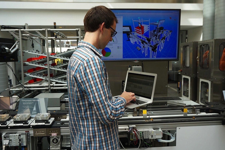 Ein Mitarbeiter des Lemgoer Instituts für industrielle Informationstechnik (inIT) der Hochschule OWL testet das Assistenzsystem mit einer Modellanlage in der Versuchsfabrik.