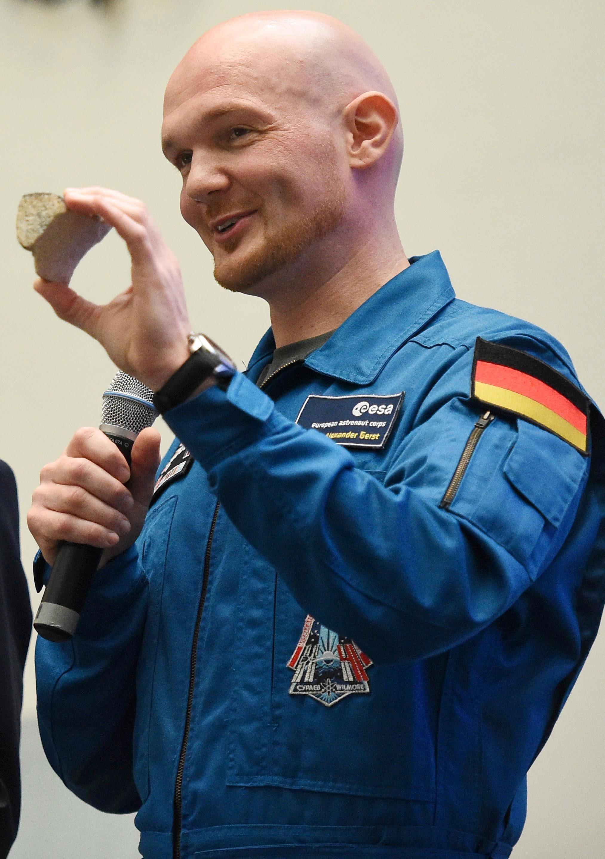 ESA-Astronaut Alexander Gerst mit dem weit gereisten Stück Sandstein aus der Fassade des Kölner Doms in der Hand.