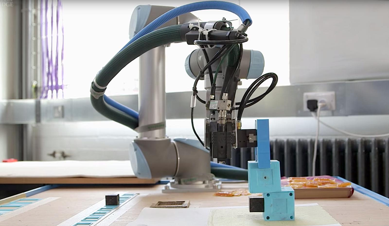 Roboterarm bei der Arbeit: Er klebt aus zwei viereckigen Kästen einen rudimentären Laufroboter zusammen.