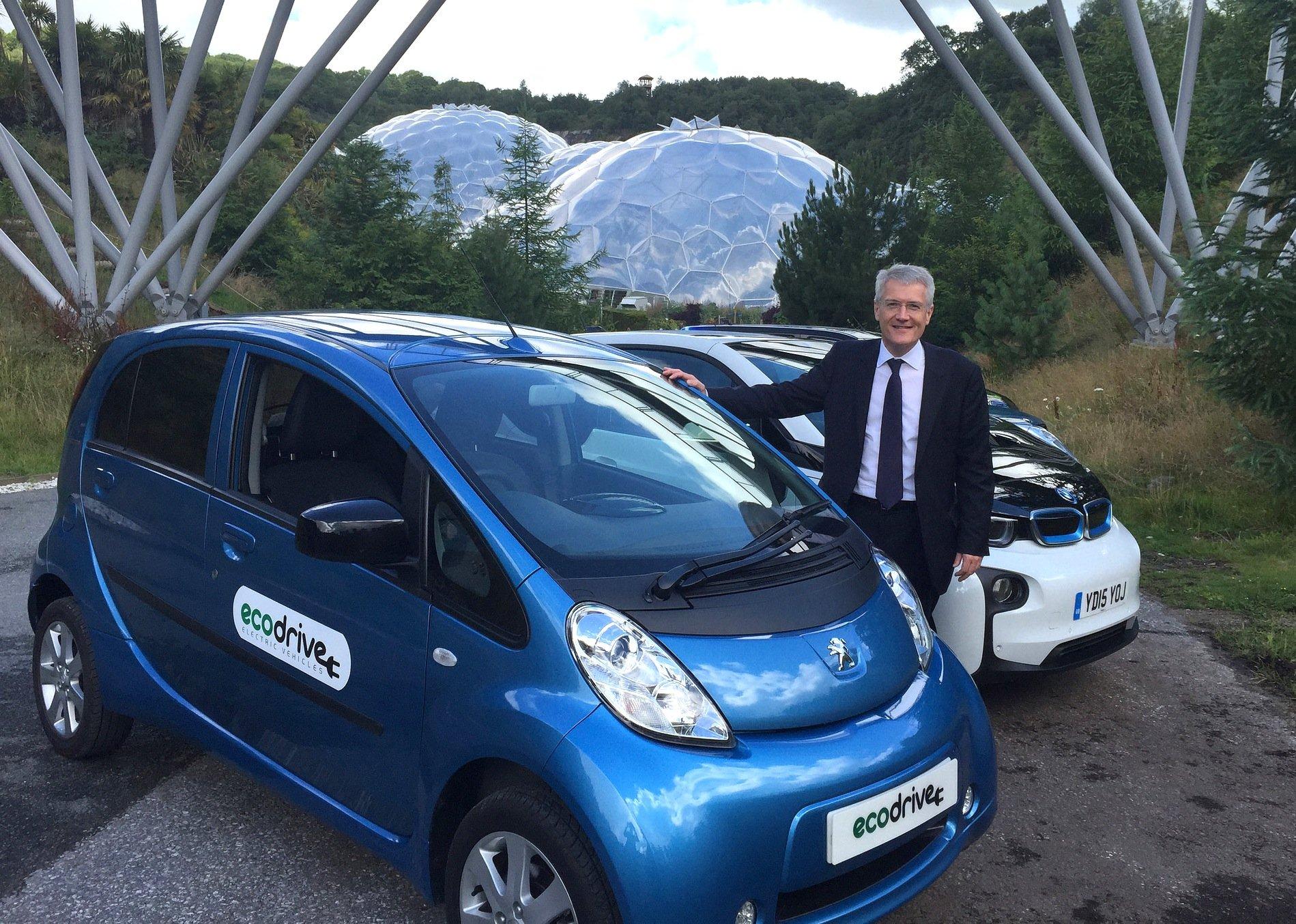 Der britische Transportminister Andrew Jones vor Elektroautos von Peugeot und BMW: Großbritannien will seine Autobahnen mit induktiver Ladetechnik ausrüsten und gibt dafür 700 Mio. € in den nächsten fünf Jahren aus.