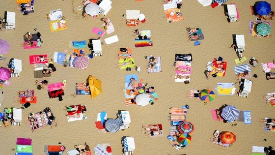 Bei Temperaturen um 35 °C sonnen sich Besucher des Berliner Strandbades Wannsee am Ufer. So entspannt wird der Blick auf die nächste Stromrechnung wohl nicht. Die Hitzewelle in ganz Deutschland verursachtMillionenkosten im Stromnetz.