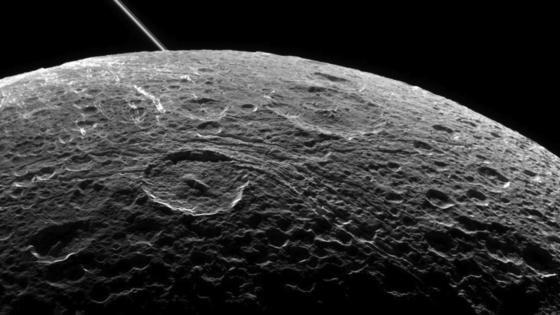 Dieses Bild von Dione hatte Raumsonde Cassini im Juni 2015 zur Erde geschickt. Im Hintergrund ist der Ring des Saturns zu erkennen.