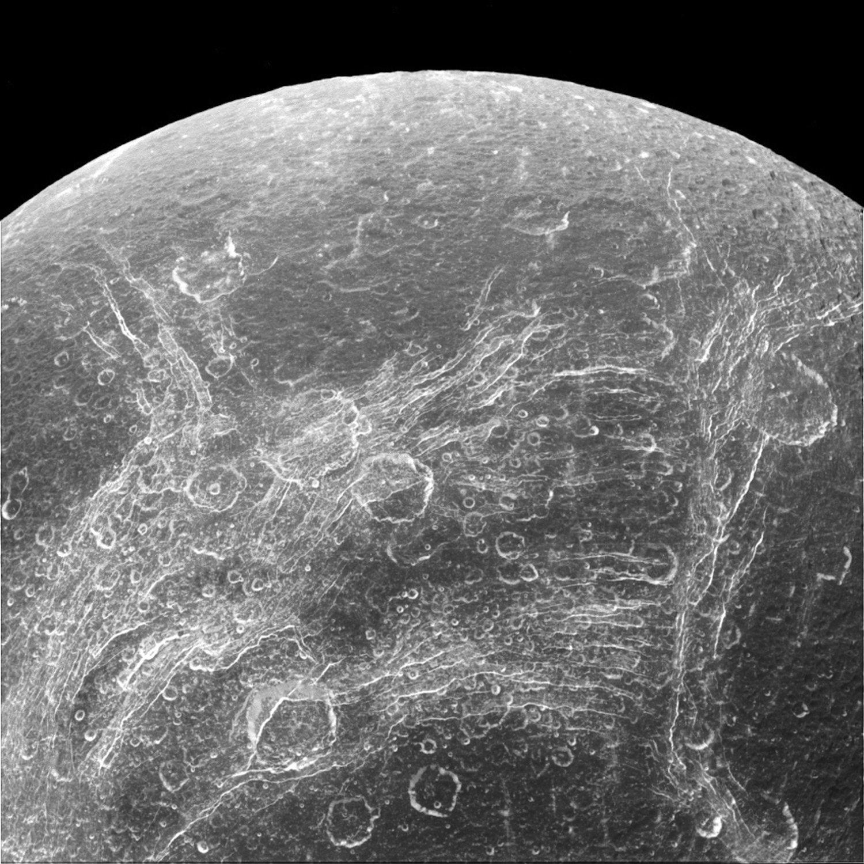 Oberfläche des Saturn-Mondes Dione: Die linearen Strukturen heißen Chasmata. Gut zu erkennen sind auch zahlreiche Einschlagkrater.
